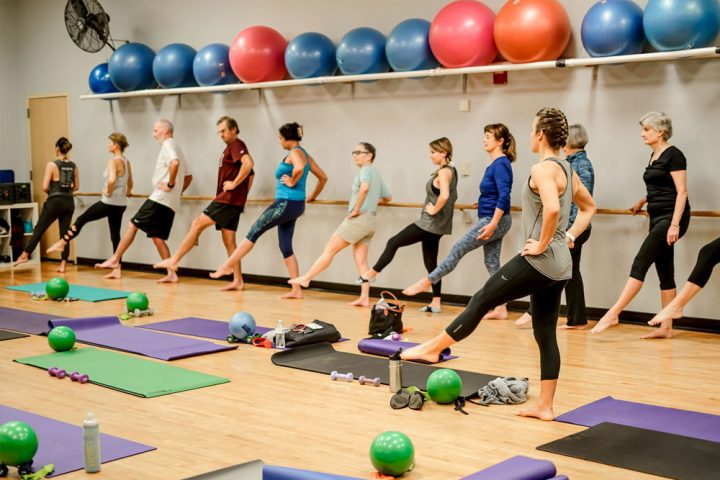Barre class instructor shows men and women how to do a leg lift.
