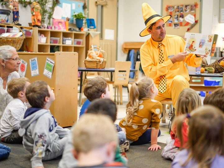 A man with a yellow hat reads a book to a group of preschool kids.