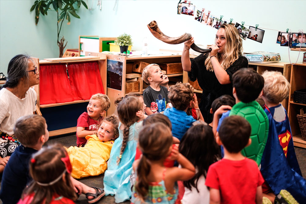 Preschool teacher blowing a shofar in front of kids in classroom