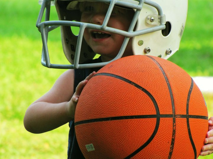A toddler child wears a football helmet and holds a basketball outside on a grass field.