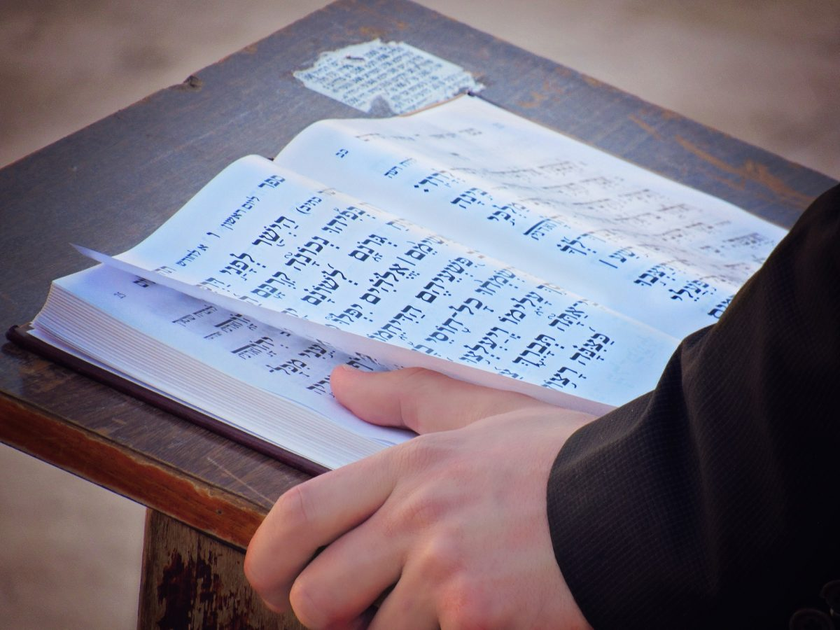 A man reading from a prayer book during a service at a synagogue