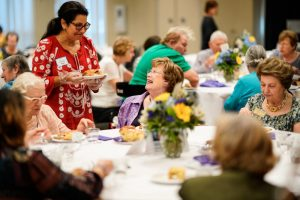 A woman wearing a red dress talks with an older woman at a table during the Adults 60+ Rosh Hashanah Luncheon.
