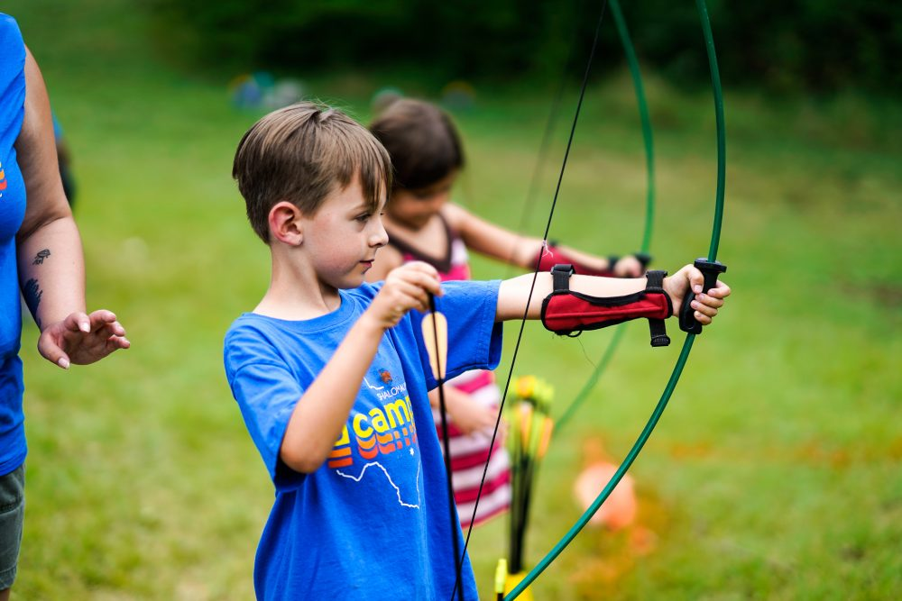 A boy and girl practice shooting a bow and arrow during archery at JCamps.