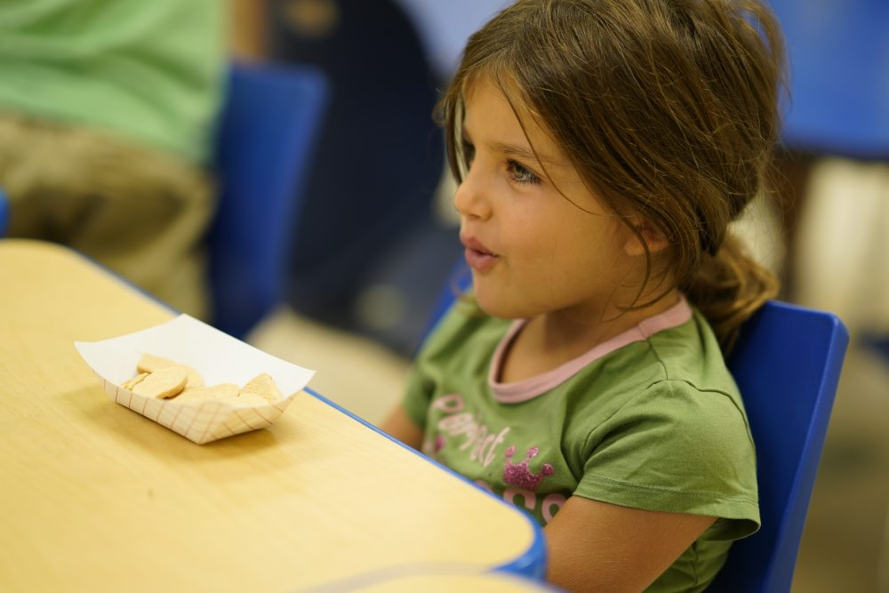 A young girl wearing a green shirt eats a snack or lunch at JCamps.