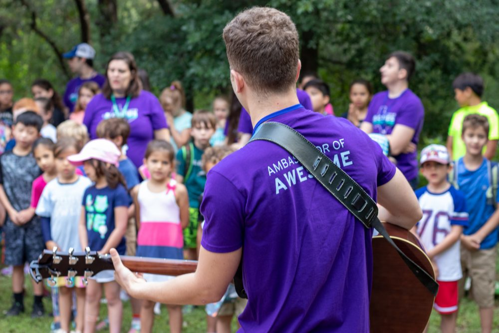 A JCamps staff member wearing a purple shirt plays the guitar for kids during Song Session.