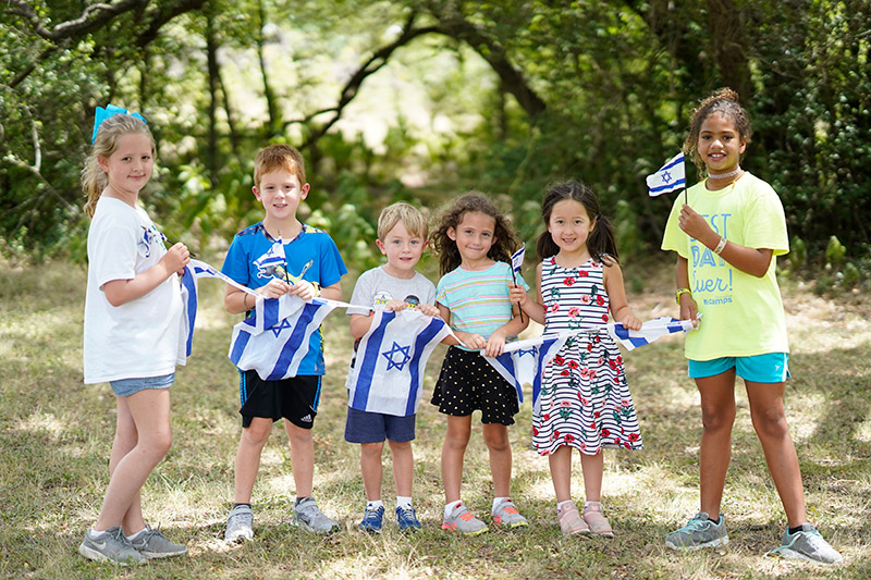 Preschool and school age kids holding a string with Israeli flags