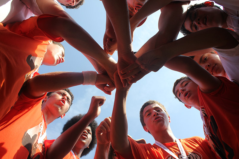 Teens at Maccabi wearing orange shirts with hands together as a team
