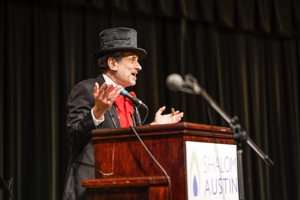 A man wearing a top hat performs in Vaudeville on stage