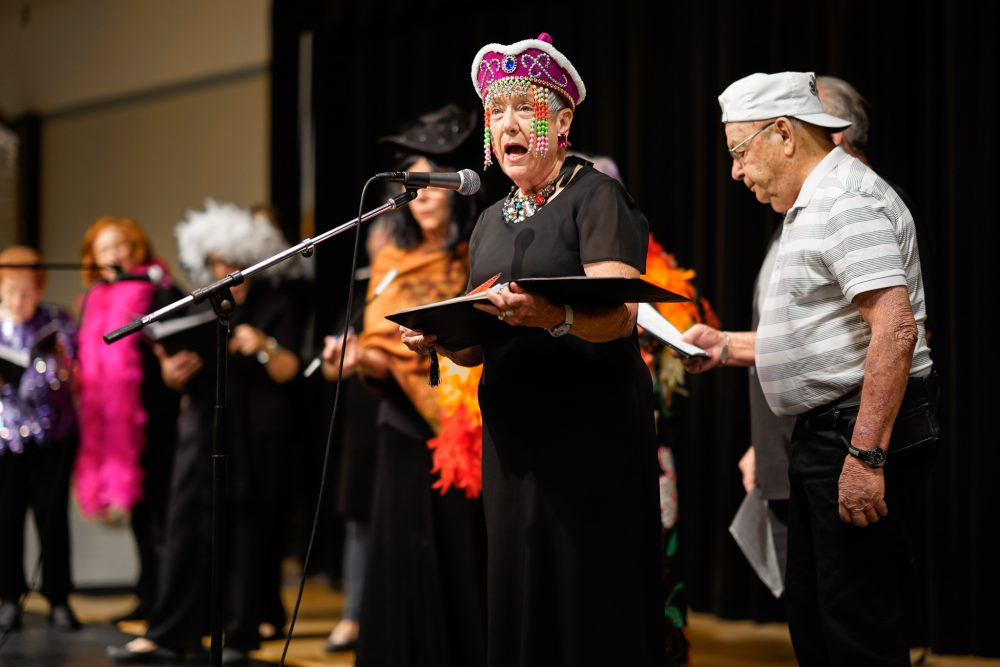 The Dells Angels Choir members hold song books and sing together on stage.