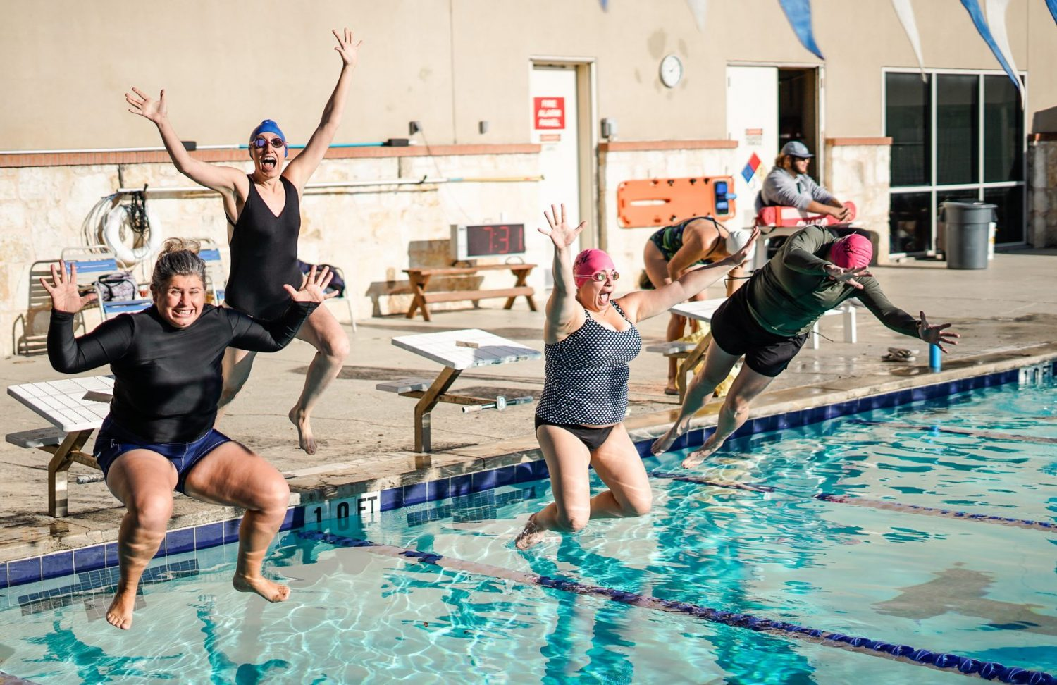 Women smiling and jumping into swimming pool