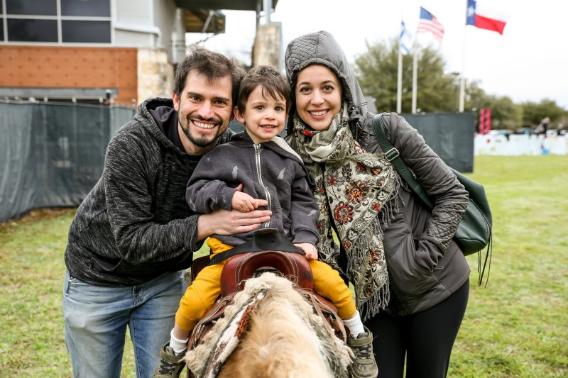 A young man and woman smile with a preschool age boy riding a pony