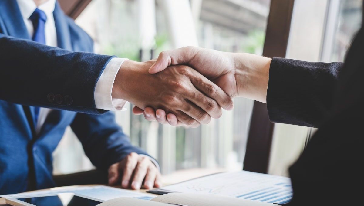 Two people wearing business suits shake hands