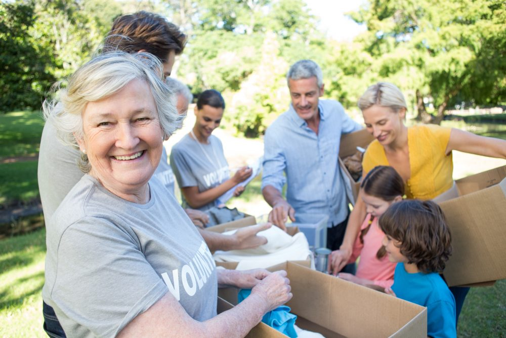 An older woman volunteer smiles as she puts donations into boxes with her family
