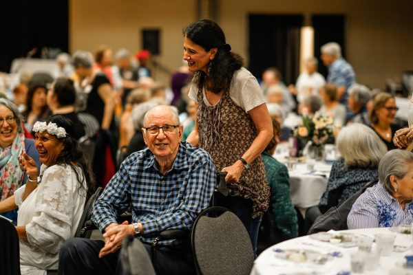 A woman pushes a man in a wheelchair at the Senior Rosh Hashanah Luncheon.