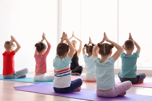 A group of children practice yoga during a class