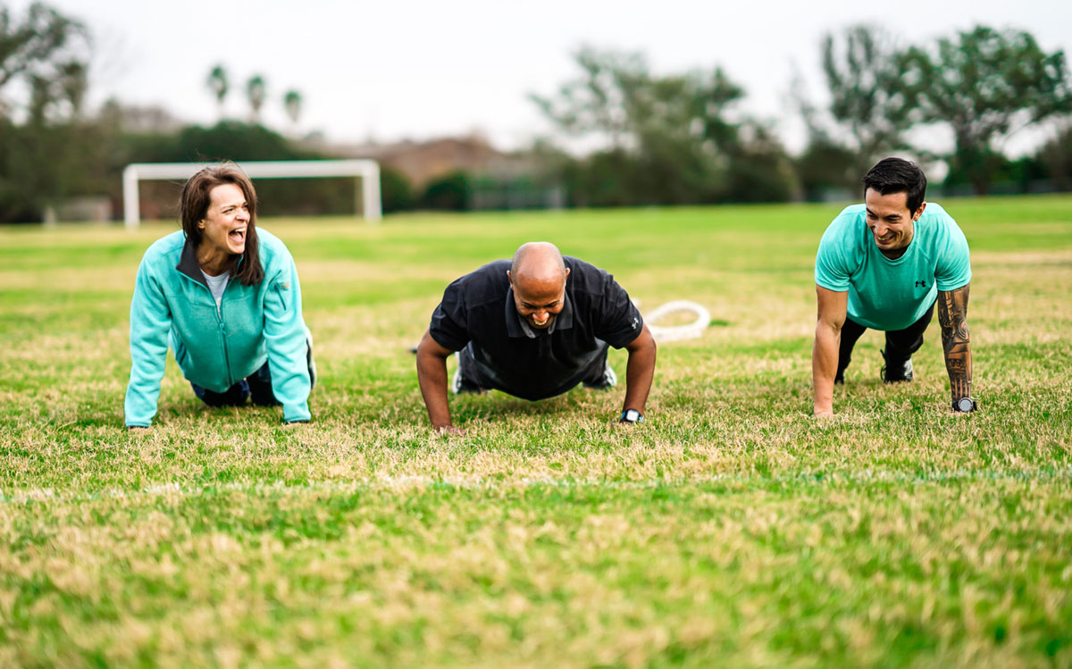 Three personal trainers doing push up and laughing on a grass field.