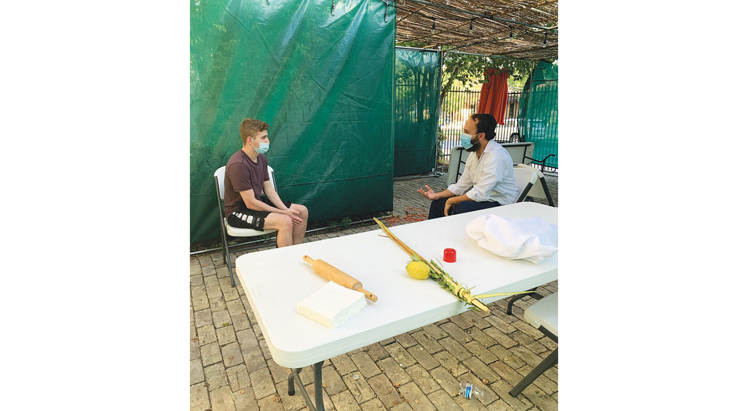 A college student sits on a chair and talks with a rabbi in a sukkah.