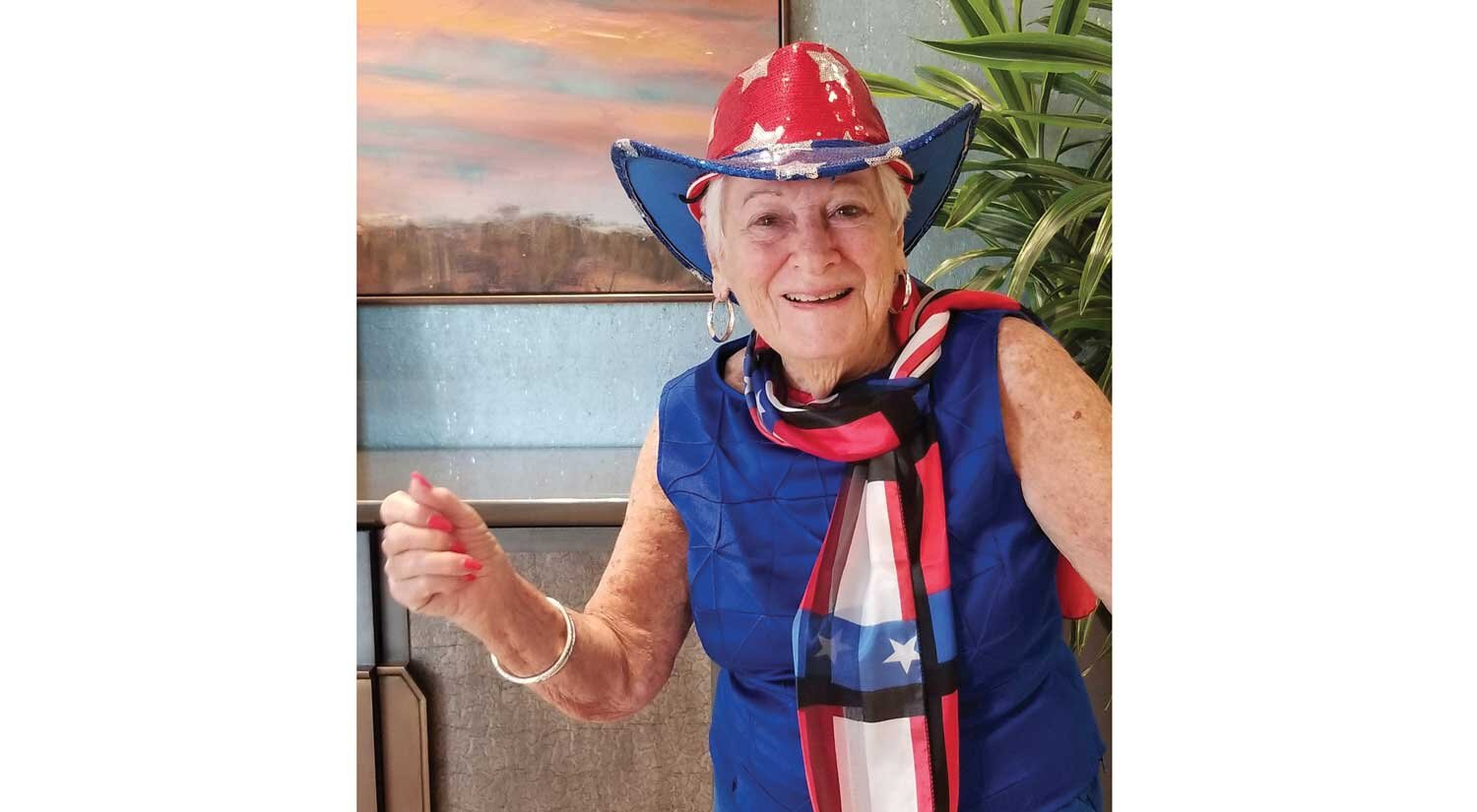 An elderly woman wearing a red, white and blue hat and Texas flag scarf smiles at the camera.