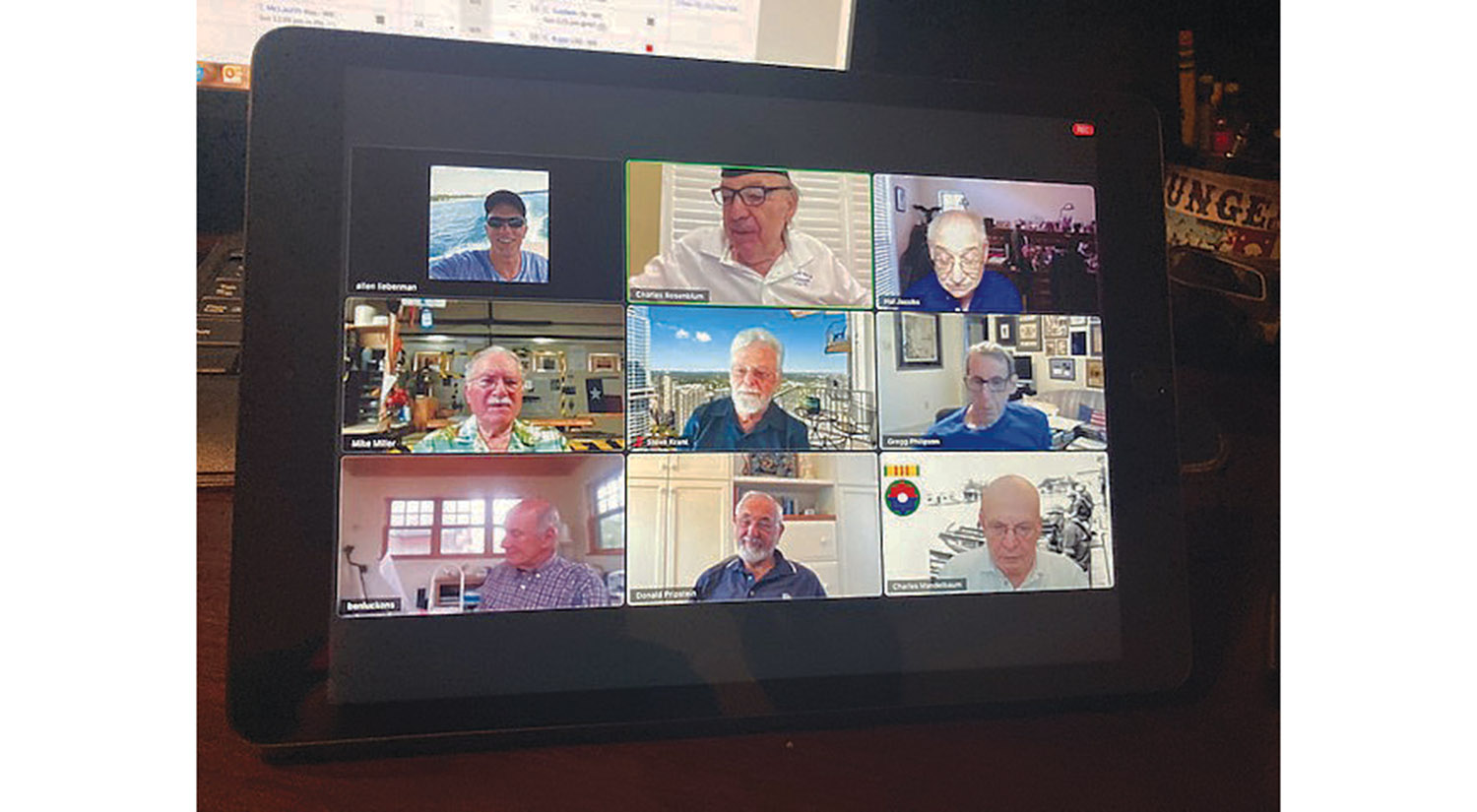 A group of 9 elderly men hold an online meeting on a video conference call.