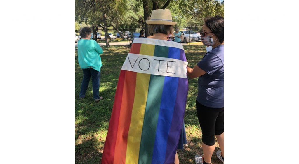Woman wears a rainbow flag with vote on it around her shoulders