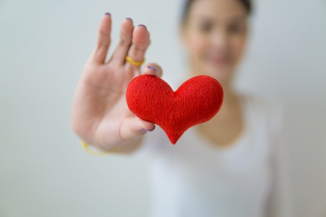 Close up of woman's hands holding a fuzzy red heart over a wood table